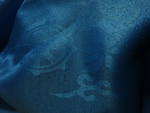 closeup of a blue scarf with a wheel motif embroidery